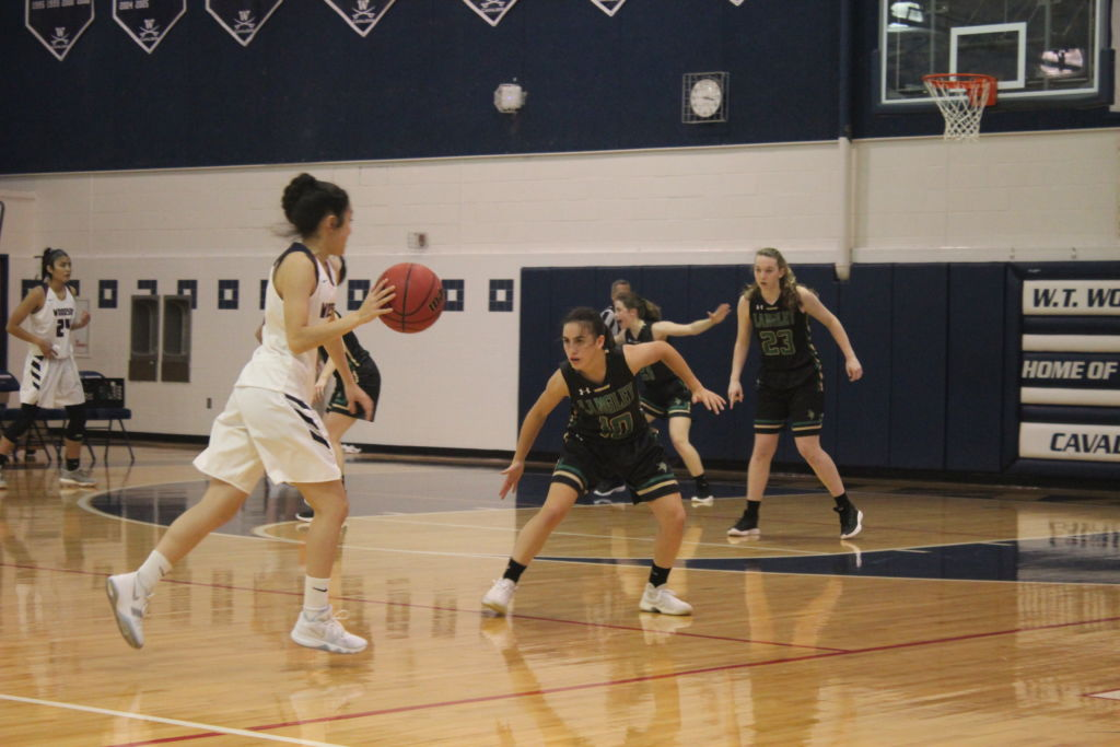 Annabeth Holsinger (9) guards Cavalier, Rachel Shurberg (12), as Kylie Allen (10) positions herself in help defense. Allen scored 11 points in the game, making her the second highest scorer of both teams.