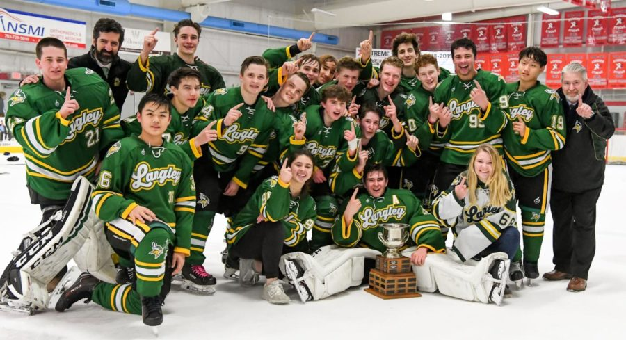 Langley Hockey Team celebrating their win with their coaches and their newly received championship cup.