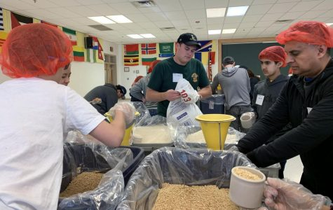 Senior John Callahan works with others to complete his service hours during the monthly Saxon Service time (Photo by Chen).