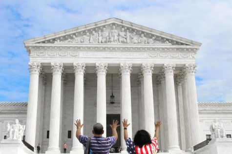 A man and wife stand before the Supreme Court, raising their hands in prayer. Over the past few weeks, hundreds of individuals have traveled to the Supreme Court to either protest the appointment of Amy Coney Barrett to the bench or demonstrate support (Photo by seniors Lexie Gagnon, Maddie Koenig, and Cole Sitilides).