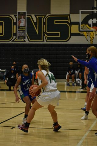 Senior Summer Thomas (#14) takes possession of  the ball during the intense game. Even with a tough fight, Langley lost by three points.