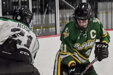 Langley hockey captain, senior Charlie Tourbaf battles for the puck in last Friday's game against Loudoun Valley/Woodgrove. Remember to download the app, LiveBarn to watch all the action during Langley hockey games (Photo by Cahill).